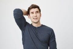 Den eftertänksamma mörkhåriga mannen i denmuff t-skjortan som poserar mot grå bakgrund, rynkar pannan framsidan, ser hänsynsfullt fotografering för bildbyråer