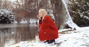 Den eftertänksamma unga flickan som tycker om vinter i en stad, parkerar arkivfoto