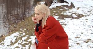 Den eftertänksamma unga flickan som tycker om vinter i en stad, parkerar royaltyfri bild