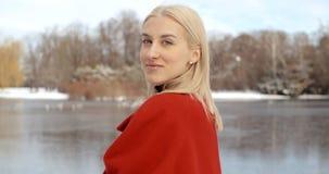 Den eftertänksamma unga flickan som tycker om vinter i en stad, parkerar royaltyfri fotografi