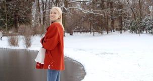 Den eftertänksamma unga flickan som tycker om vinter i en stad, parkerar royaltyfria foton