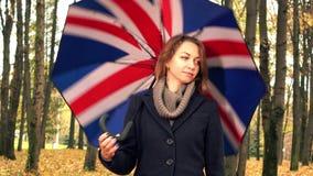 Den eftertänksamma unga kvinnan som går med britt flagga-som paraplyet i höst, parkerar gränden skott för steadicam 4K lager videofilmer