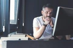 Den eftertänksamma vuxna mannen sitter på hans skrivbord arkivbild