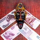 Den egyptiska souvenirmaskeringen och de egyptiska pengarna, på en röd baksida Royaltyfri Fotografi