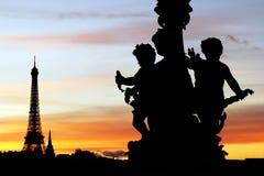Den Eiffeltorn- och Alexandre III bron skulpterar konturer under en parisisk solnedgång Royaltyfria Foton
