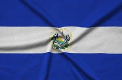 Den El Salvador flaggan visas på ett sporttorkduketyg med många veck Baner för sportlag royaltyfri fotografi