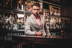 Den eleganta ansade mannen dricker alkohol på stången arkivfoton