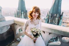Den eleganta bruden med den brud- buketten poserar på tornbalkongen av den gamla gotiska domkyrkan Royaltyfri Foto
