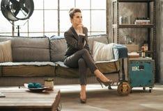 Den eleganta brunettaffärskvinnan sitter på soffan i vind royaltyfri bild