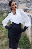Den eleganta brunetten bär den vita skjortan, läderkjolen och handskar Royaltyfri Bild