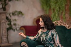 Den eleganta caucasian flickan i lyxiga långa paljetter snör åt klänningen med en grön fluffig boa i hennes händer som poserar i  fotografering för bildbyråer
