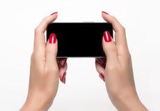 Den eleganta kvinnan räcker att rymma en smartphone royaltyfri foto