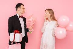 Den eleganta mannen i en dräkt, ger en ask med en gåva och en bukett av blommor, till en härlig kvinna, på en rosa bakgrund kvinn arkivfoton