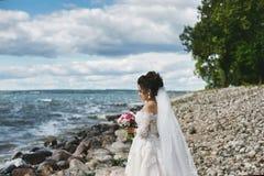 Den eleganta och trendiga flickan för den brunettplus-formatet modellen i det stilfullt snör åt bröllopsklänningen med den stilfu fotografering för bildbyråer