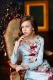 Den eleganta prinsessan i blått klär med krabbt hår och en krona på henne fotografering för bildbyråer