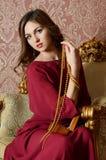 Den eleganta sinnliga unga kvinnan i en bordeauxklänning royaltyfria bilder