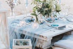 Den eleganta tabellen ställde in i blåa pastell för ett strandbröllop arkivfoton