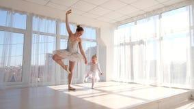 Den eleganta unga ballerina undervisar hennes lilla dotterdans i studio arkivfilmer