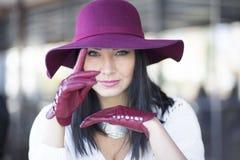 Den eleganta unga kvinnan i en burgundy hatt och handskar sitter på en tabell Arkivbild