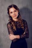 Den eleganta unga kvinnan i svart snör åt dres med långt lockigt hår Royaltyfria Foton