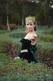 Den eleganta unga kvinnan klädde som drottningen som går i trädgård Fotografering för Bildbyråer