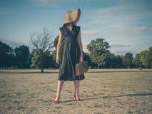 Den eleganta unga kvinnan med portföljanseende parkerar in arkivfoto