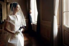 Den eleganta ursnygga bruden som försiktigt under ser, skyler på den stilfulla grooen royaltyfria foton