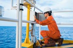 Den elektrisk och instrumentteknikeren är kontroll på belysning av navigeringstödsystemet på plattformen för fossila bränslenwell fotografering för bildbyråer