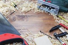 Den elektriska figursågen med många trätegelstenar som är fulla av sågspån på den gamla skrapade trätabellen, arbete bearbetar be Royaltyfria Bilder