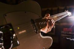 Den elektriska gitarren i gitarrist räcker closeupen royaltyfri foto