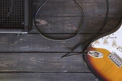 Den elektriska gitarren och svartförstärkaren förband vid kabel på trä Arkivbild