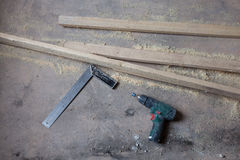 Den elektriska hålapparaten med drillborren är på det smutsiga och dammiga trägolvet under under-renovering, omdana och konstrukt Arkivbild