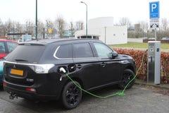 Den elektriska Mitsubishi bilen laddar på en laddande punkt royaltyfria foton