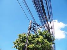 Den elektriska polen förbinder till de elektriska trådarna för hög spänning på bakgrund för blå himmel Royaltyfri Foto
