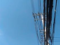 Den elektriska polen förbinder till de elektriska trådarna för hög spänning på bakgrund för blå himmel Arkivfoton