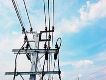 Den elektriska polen förbinder till de elektriska trådarna för hög spänning på bakgrund för blå himmel Royaltyfria Foton