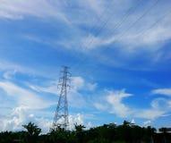 Den elektriska polen förbinder till de elektriska trådarna för hög spänning på bakgrund för blå himmel Arkivbilder