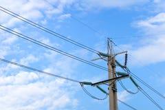 Den elektriska polen med blå himmel och vit fördunklar Arkivfoto