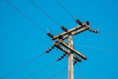 Den elektriska stolpen vid den lokala vägen med kraftledningen kablar Royaltyfria Bilder