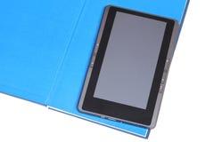 Den elektroniska boken som ligger på den öppnade pappers- boken Arkivfoton