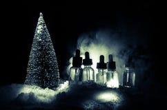 Den elektroniska cigaretten med vapeflytande och julgarneringar på bokeh tänder bakgrund Fotografering för Bildbyråer