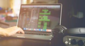 Den elektroniska musikern är jordbruksproduktermusik på bärbara datorn Arkivfoto
