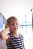 Den elementära flickan med ögon stängde lyssnande musik till och med hörlurar Arkivfoto