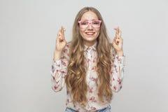Den emotionella flickan som visar bra lycka, undertecknar henne fingrar som ser ca fotografering för bildbyråer