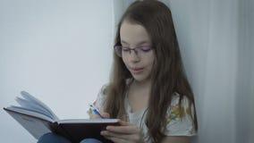 Den emotionella lilla flickan med exponeringsglas skriver i hans dagbok på fönstret lager videofilmer