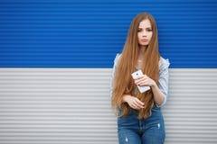 Den emotionella ståenden av en vuxen nätt blond kvinna med ursnyggt extra långt hår som utomhus poserar mot blåa grå färger, gjor Royaltyfria Bilder