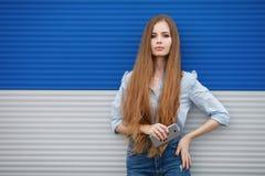 Den emotionella ståenden av en vuxen nätt blond kvinna med ursnyggt extra långt hår som utomhus poserar mot blåa grå färger, gjor Arkivbilder