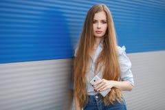 Den emotionella ståenden av en vuxen nätt blond kvinna med ursnyggt extra långt hår som utomhus poserar mot blåa grå färger, gjor Royaltyfri Fotografi