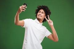 Den emotionella unga afrikanska lockiga mannen gör selfie vid mobiltelefonvisningfred att göra en gest Arkivfoto