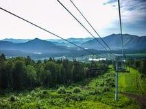 Den Emtpy chairliften skidar in semesterorten Skott i sommar med grönt gräs och ingen snö Fotografering för Bildbyråer
